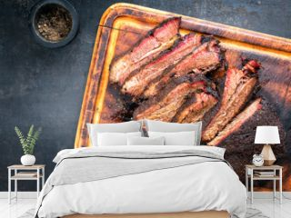 Traditional smoked barbecue wagyu beef brisket as piece and sliced offered as top view on an old cutting board with copy space left
