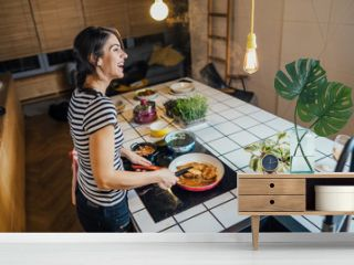 Young woman tasting a healthy meal in home kitchen.Making dinner on kitchen island standing by induction hob.Preparing fresh vegetables,enjoying spice aromas.Eating in.Passion for cooking.Keto diet
