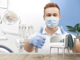 Always professional! Professional dentist wearing protective mask and gloves showing thumbs up posing at his dental clinic copyspace professionalism gesture approved confidence medicine health people
