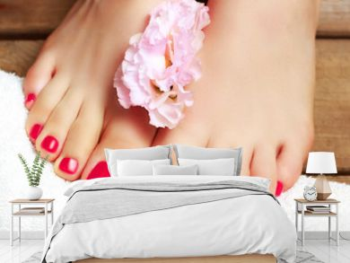 Pink pedicure with flower close-up, isolated on a wooden background, top view