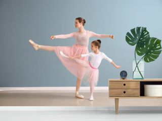Little ballerina with coach against color wall