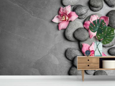 Zen stones and exotic flowers on dark background, top view with space for text
