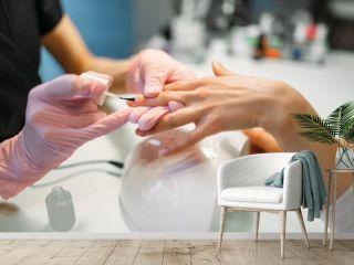 Manicure master applying nail varnish