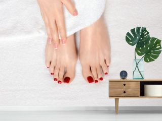 Classic red pedicure and manicure. Female feet and hand on white terry towel, natural skin tone. Woman in beauty salon.