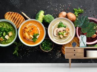 Assortment of colored vegetable cream soups. Dietary food. On a black stone background. Top view. Free copy space.