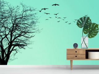 The silhouette of the tree and a flock of birds on a turquoise background.