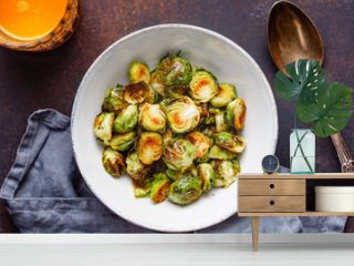Top view of a ceramic bowl with roasted brussel sprouts on a table. The concept of healthy vegetarian eating.