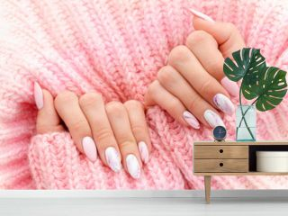 Female hands manicure close up view on pink knitted sweater background. Nail painting effects. Manicure salon banner concept