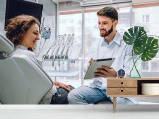 People, medicine, stomatology and health care concept - happy male dentist showing tablet computer to woman patient at dental clinic office.