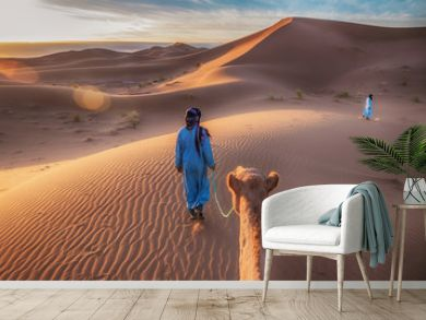 Two Tuareg nomads dressed in traditional long blue robes, lead a camel through the dunes of the Sahara Desert at sunrise in Morocco.