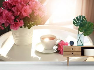 Pot with beautiful blooming azalea and cup of tea on table
