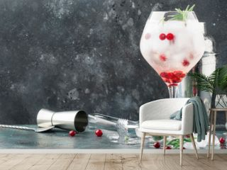 Cranberry cocktail with ice, fresh rosemary and red berries in big wine glass, bar tools, gray bar counter background, copy space, selective focus
