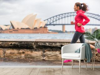 Runner fit active lifestyle woman jogging on Sydney Harbour by the Opera house famous tourist attraction landmark. City life.