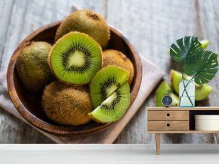 Fresh kiwi fruit in the bowl on wooden background