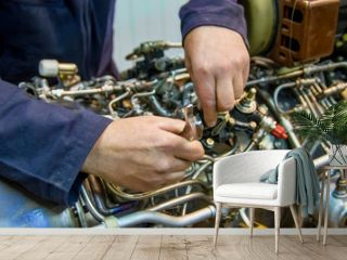 Hands working with a wrench, helicopter engine repair