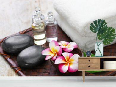 tropical spa resort concept  plumeria, hot stones, towels, and massage oils