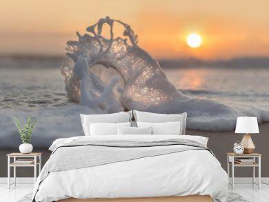 Glaskugel am Strand in der Schaumwelle im Sonnenuntergang