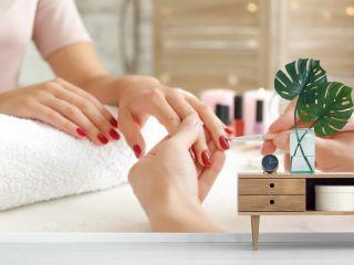 Woman getting professional manicure in beauty salon, closeup