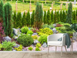 Landscape design in home garden. Landscaping with plants and flowers in backyard.