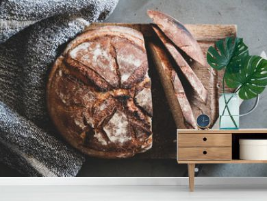 Flat-lay of freshly baked sourdough bread loaf and bread slices on rustic wooden board over grey concrete table background, top view