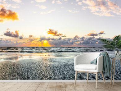 Schöner Sonnenuntergang am Meer mit Wolken und Wasserspiegelung