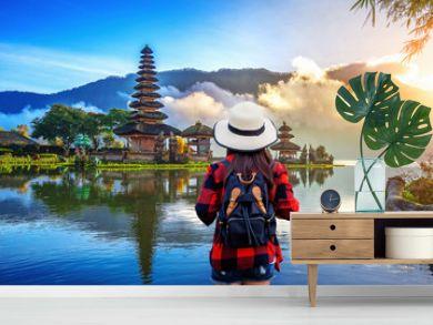 Woman traveler with backpack looking to pura ulun danu bratan temple in Bali, indonesia.