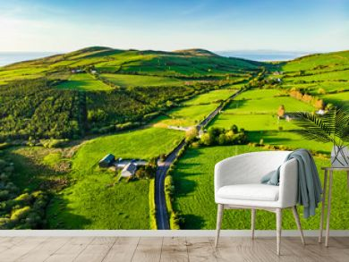 Aerial view of endless lush pastures and farmlands of Ireland. Beautiful Irish countryside with green fields and meadows. Rural landscape on sunset.