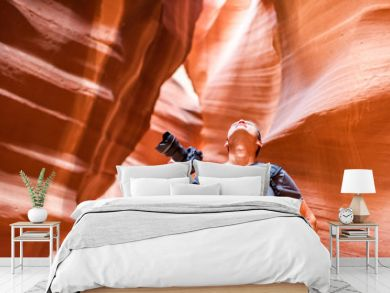 Antelope slot canyon with photographer man holding camera looking up at abstract formations of red orange rock layers sandstone in Page, Arizona