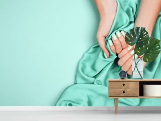 Hands of a young girl on a mint silk cloth, manicure on a trendy background , green polish