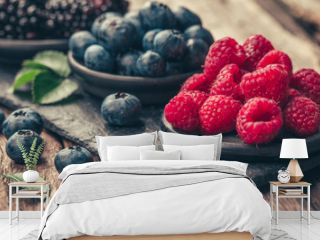 Fresh berries with raspberries, blueberries, blackberries in bowl on a stone stand on wood background.