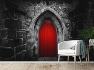 Scary pointy red wooden door in an old and wet stone wall building with cross, skull and bones at both sides. Concept mystery, death and danger.