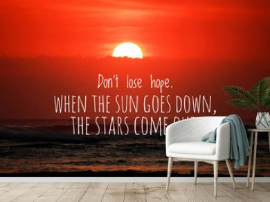 Inspirational quote - Do not lose hope. When the sun goes down, the stars come out. With blurry sunset background over the sea horizon. Half of the sun behind the clouds. Words of wisdom concept.