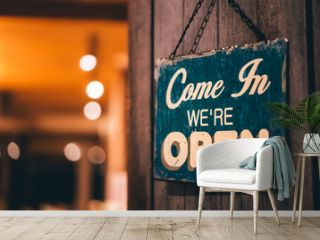 Open sign broad hanging on wood door front of cafe.