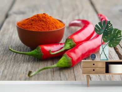 Whole and ground to powder red chili pepper on wooden kitchen table.