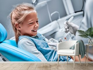 The dentist tells the child about oral hygiene and shows an artificial jaw and toothbrush