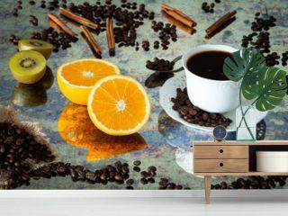 Coffee with cinnamon sticks, orange and kiwi in a cup