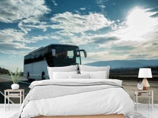 White Modern comfortable tourist bus driving through highway at bright sunny sunset. Travel and coach tourism concept. Trip and journey by vehicle