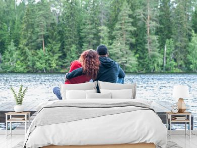 Guy and a girl sit hugging on the pier of a beautiful lake. The concept of love, the summer mood , banner