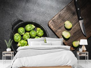 Fresh green brussels sprouts in black bowl and cutting board with knife on dark background. Overhead shot.