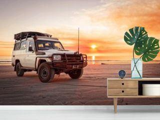 Outback relaxing adventure with 4WD vehicle at the beach of an ocean at sunrise