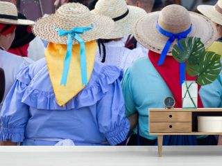 Back of anonymous women in traditional costumes at local festival in Gran Canaria, Spain. Popular celebration with people on wicker hats and colorful scarfs in Las Palmas city, Canary Islands