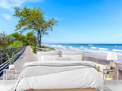 Wooden walkway along beautiful white sand beach with blue sea near Kolobrzeg, Baltic Sea coast, Poland