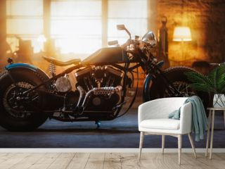 Custom Bobber Motorbike Standing in an Authentic Creative Workshop. Vintage Style Motorcycle Under Warm Lamp Light in a Garage. Profile View.