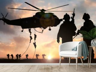 Military commando special operation helicopter drops in silhouette at dusk