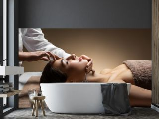 wellness, beauty and relaxation concept - beautiful young woman lying with closed eyes and having face and head massage at spa