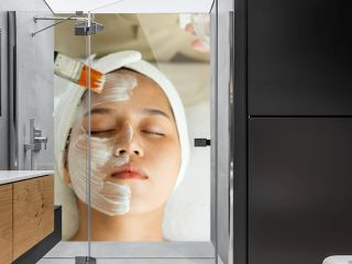 Beautiful young Asian Woman getting facial care by beautician at spa salon, Face peeling mask, spa beauty treatment, skin care concept