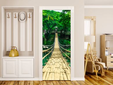 Bamboo hanging bridge over river in tropical forest