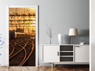 A train on the railroad tracks during a beautiful sunrise. Lyon, France.