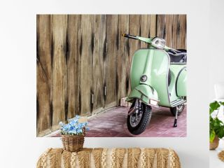 Green scooter against old house. wood wall mossy surface of building as background. Urban street in Thailand, Asia. Moped parked at moldy wood wall. Asian lifestyle and popular transport.