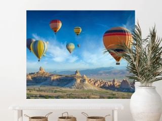 Colorful hot air balloons fly in blue sky over amazing valleys with fairy chimneys in Cappadocia, Turkey